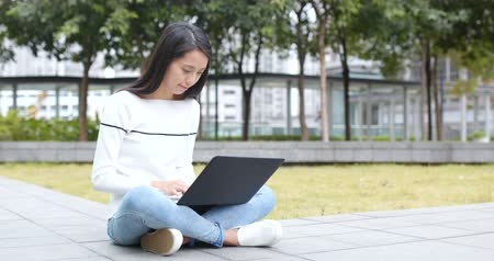 city park : Woman using on laptop computer Stock Footage