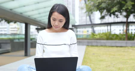 Student woman doing homework on notebook computer at outdoor