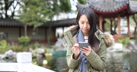 pletení : Woman use of mobile phone in the Chinese garden