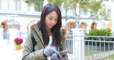 Woman wearing knit gloves and use of mobile phone at winter time