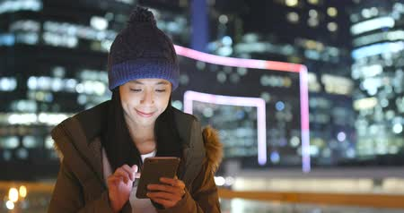編み物 : Woman wearing winter knit hat and jacket with using mobile phone over beautiful cityscape background 動画素材