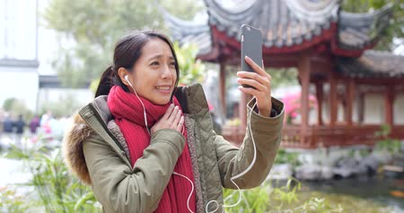 make friends : Woman talk to cellphone with earphone in Chinese garden