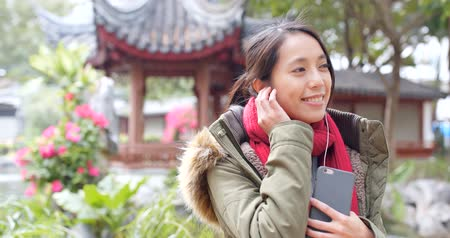 Woman listen to music and wearing winter jacket at Chinese garden