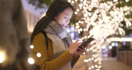 Asian Woman use of cellphone at night in the city