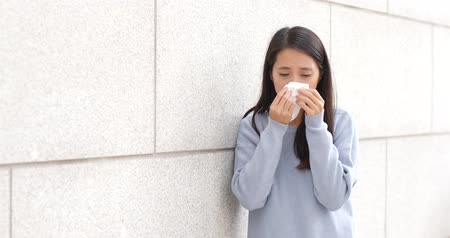 infecção : Woman sneezing at outdoor Stock Footage