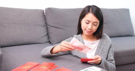 renminbi : Woman putting banknote into lunar new year red packet Stock Footage