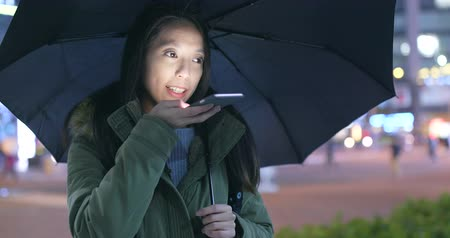 voz : Woman sending audio message on cellphone and bringing black umbrella at night