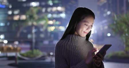 e mail : Asian Woman use of smart phone at night Stock mozgókép