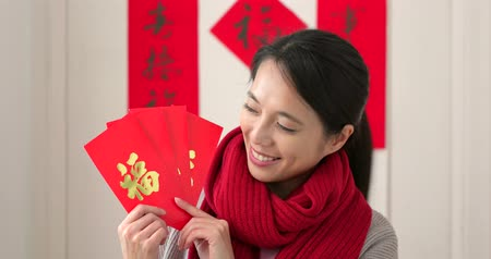 meio : Chinese woman holding red packet and feeling happy