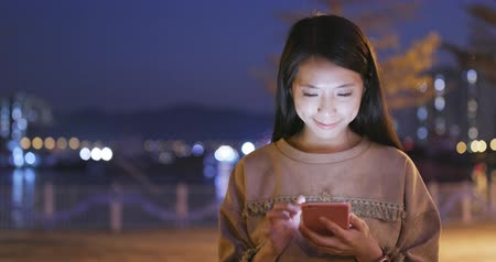 japonsko : Asian Woman use of mobile phone in city in the evening
