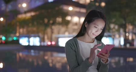 hong kong : Young woman use of mobile phone in city at night Stock Footage