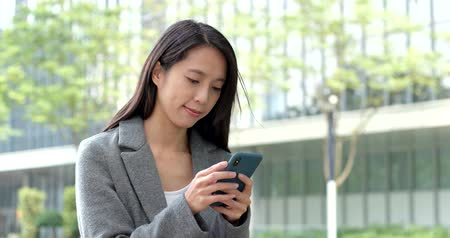 részvény : Businesswoman use of smart phone in city