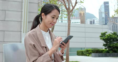 verificar : Business woman using mobile phone at outdoor