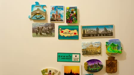 lodówka : hands place many magnets on refrigerator in time lapse