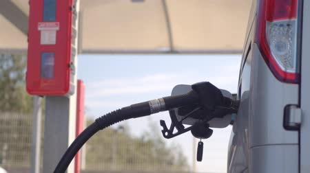 filling station : Fuel nozzle inserted in car diesel tank and refueling Stock Footage