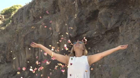 para : Beautiful blonde woman in white dress throwing up rose petals Stock Footage