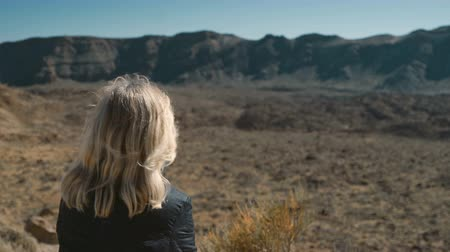 umutlu : lonely girl thoughtfully sitting surrounded by a volcanic landscape Stok Video