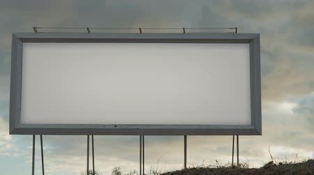 poste de sinalização : Blank white billboard on the background of the sky with moving clouds in the sunset light Vídeos