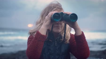 cheerless : portrait of mature woman with binoculars on a storm background against a dramatic sky background Stock Footage