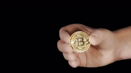 Male hand is holding a golden bitcoin cryptocurrency coin Стоковые видеозаписи