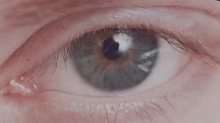 macro video of the eye and part of the face of a 25-30 year old caucasian man