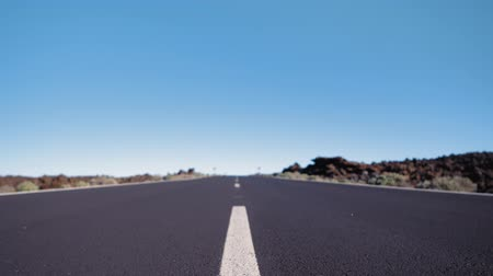 Close-up shot of a smooth motion over the asphalt surface of the road with a road marking line Стоковые видеозаписи