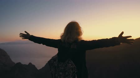 the woman meets the sunset on the mountain top and spreads her arms wide with delight