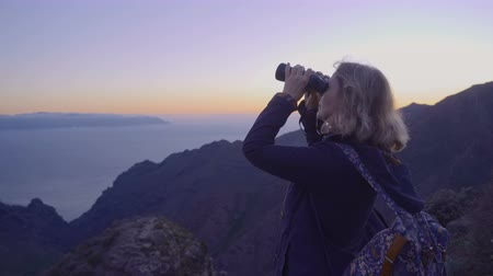Mature woman in hiking adventures on a mountain top looking at the horizon through binoculars Стоковые видеозаписи