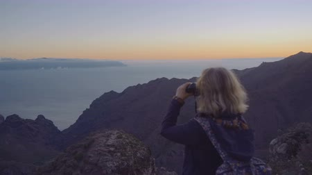Attractive mature woman in hiking adventure on a mountain top looking at the horizon through binoculars