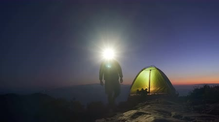outlook : an adult man in an adventure trip to the top of a mountain set up a tourist tent for an overnight stay