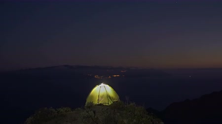 the tourist tent glows in the night on the high coast of the ocean opposite the night lights of the other island. Strong gusts of wind rocking the tent