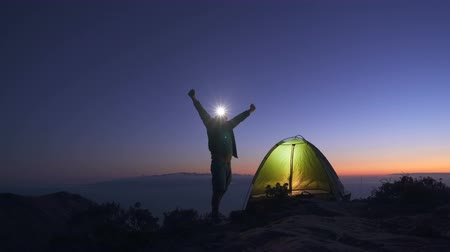 outlook : Joyful tourist set up a tent on a mountain top at dusk after sunset and preparing to spend the night outdoors
