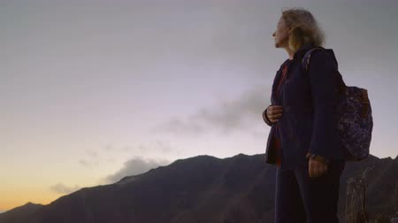 Mature woman on a high mountain landscape watching the sun set over the horizon