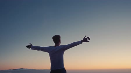 Conceptual video of the winner . A man raises his hands up, standing on a mountain top, above the clouds and blowing strong wind Стоковые видеозаписи