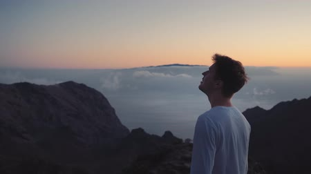 the man thoughtfully looks in the sky on the edge of the earth on top of the mountains above the clouds