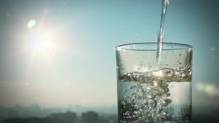 enchimento : conceptual footage of pouring water on a background of blurred city and sun, full HD     Vídeos