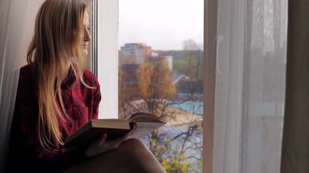 intelecto : Beautiful young blonde woman reading a book and sitting on the windowsill Stock Footage