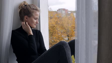 sill : Sad woman looking at window and sitting on windowsill Stock Footage