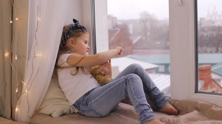 sill : Cute girl playing with her teddy bear and sitting on window sill