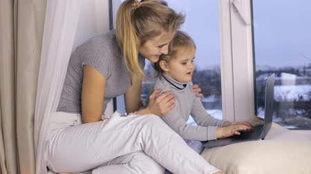 sill : Cute girl with her mother using laptop computer