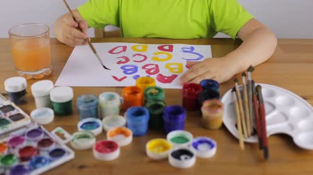 school children : Child learns to write letters with paint