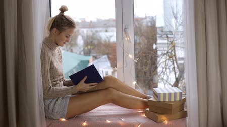 ler : Girl in a sweater reads a book Vídeos