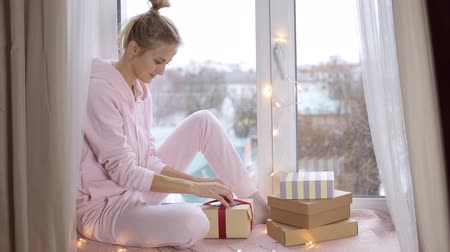 Girl in home suit unpacks a gift Stock Footage