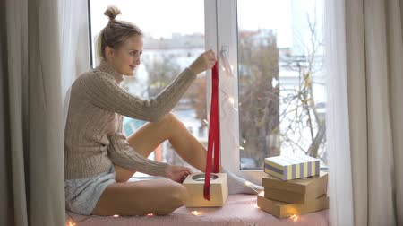 anniversary congratulations : Girl unpacks a gift while sitting