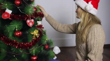 Girl in Santa hat decorates a Christmas tree Stockvideo