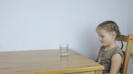 pravidelný : Girl drinks a tablet with water while sitting at the table