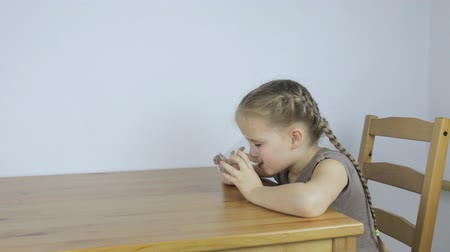 Girl eagerly drinks water while sitting in the kitchen Stock Footage