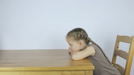Girl is bored alone, sitting at the table Stock Footage