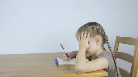 Little girl learns and writes assignments in a notebook Stockvideo
