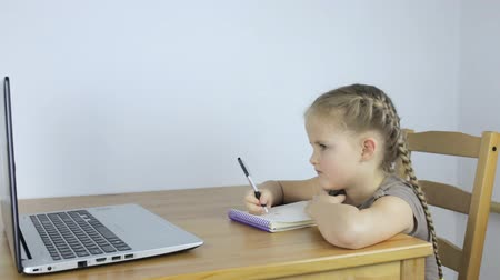 Little girl studying online, writes in a notebook